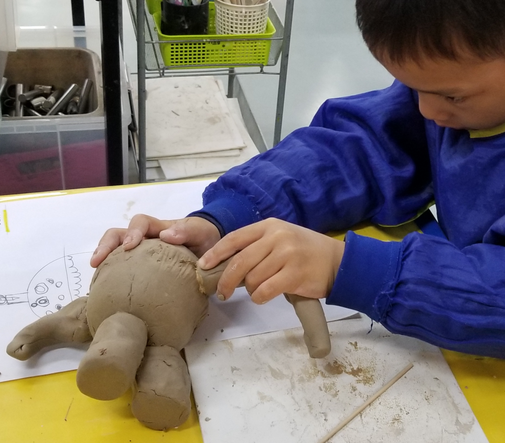 making a clay creature at the Art Lab